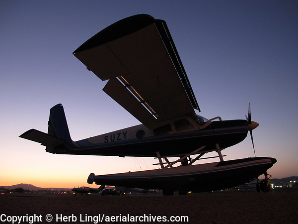 Helio Courier, N295HC, an H-295 on floats at Gillespie Field (SEE), El Cajon, San Diego County at dusk.  Features which make the Helio Courier an excellent STOL aircraft and outstanding seaplane are visible in this photograph.  They include the slats which extend from the leading edge of the wing, and the large flaps.