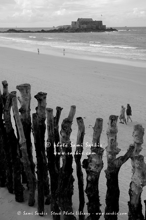 Wooden posts in a row on the beach in front of Fort National, Saint-Malo, Brittany, France.