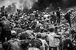 """SHEJAIYA- MAY 14: On the 30th of March, demonstrations called """"the Great March of Return"""" were organized by the civil society of Gaza to protest the blockade and demand the return of Palestinian refugees on their land. But violence between protesters and Israeli soldiers posted across the border has quickly erupted. On 14th May 2018, after the Shebab put fire on a lot of tires, a crowd advanced to the fence while trying to be covered by the smoke and escape from the Israeli shots. That day, Israeli soldiers killed 60 Palestinians and wounded over a thousand as the demonstrations coincided with the controversial opening of the U.S. Embassy in Jerusalem.<br /> <br /> SHEJAIYA - 14 MAI: Le 30 mars 2018, la société civile de Gaza a organisé des manifestations dénommées «la grande marche du retour» pour protester contre le blocus et exiger le retour des réfugiés palestiniens sur leurs terres. Mais des violences entre les manifestants et les soldats israéliens postés de l'autre côté de la frontière a rapidement éclaté. Le 14 mai 2018, après que le Shebab aient mis le feu à des pneus, une foule s'est avancé près des barrières israéliennes tout en se cachant des snipers.  Ce jour-là, des soldats israéliens ont tué 60 Palestiniens et blessé plus d'un millier alors que les manifestations coïncidaient avec l'ouverture controversée de l'ambassade américaine à Jérusalem."""