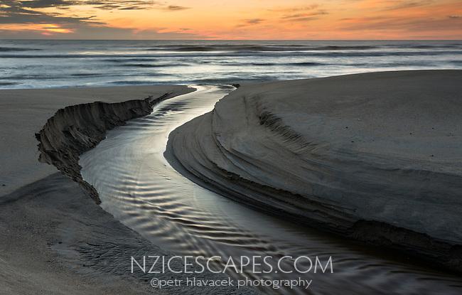 Creek flowing into sea at sunrise near Karamea, Kahurangi National Park, Buller Region, West Coast, New Zealand, NZ
