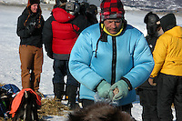 Martin Buser gives meat snacks to his dogs at Unalakleet. Photo by Jon LIttle.