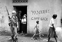 """Food distribution in front of """"Yankees come back"""" sign, Santo Domingo, May 9, 1965.  Jack Lartz.  (USIA)<br /> NARA FILE #:  306-DR-20-33<br /> WAR & CONFLICT BOOK #:  381"""