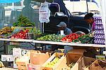 VENDOR SELLS FRUITS AND VEGETABLES AT FLEA MARKET