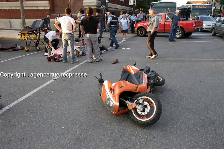 August 2008 File Photo-<br /> Montreal city firemen help paramedic treat a critically wounded person on the scene of a motorcycle accident.<br /> <br /> PHOTO : Pierre Roussel - Agence Quebec Presse