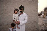 Marsh Arabs. Southern Iraq.  Marsh Arab man with daughters outside his adobe home banks of river Tigris. 1984. He has three wives, see that image