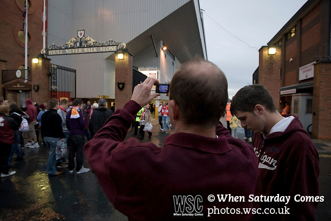 Liverpool 2 Northampton Town 2, 22/09/2010. Anfield, League Cup third round. A Northampton Town fan taking a photograph of the Shankly Gates at Anfield, before his team's Carling Cup third round tie away to Liverpool. The visitors from English League 2 defeated Premier League Liverpool on penalty kicks after a 2-2 draw after extra time in one of the biggest shock results in either clubs histories. Photo by Colin McPherson.