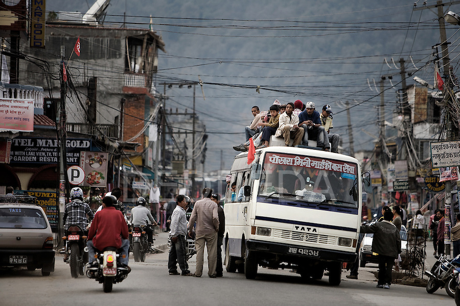 People ride on the roof of a transit bus in the Lakeside District of Pokhara, Nepal.