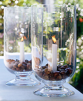 Glass storm lanterns have been filled with chestnuts and acorns to create stunning candle holders