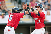 Oklahoma City RedHawks left fielder Preston Tucker (12) high fives teammate Oklahoma City RedHawks second baseman Ronald Torreyes (5) after scoring during the Pacific League game against the Colorado Springs Sky Sox at the Chickasaw Bricktown Ballpark on August 3, 2014 in Oklahoma City, Oklahoma.  The RedHawks defeated the Sky Sox 8-1.  (William Purnell/Four Seam Images)