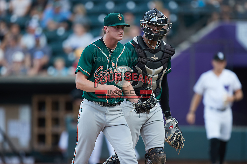 Greensboro Grasshoppers starting pitcher Quinn Priester (15) and catcher Blake Sabol (35) walk off the field between innings of the game against the Winston-Salem Dash at Truist Stadium on August 13, 2021 in Winston-Salem, North Carolina. (Brian Westerholt/Four Seam Images)