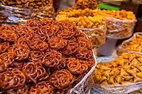 Fes, Morocco.  Pastries for Sale in the Medina, Fes El-Bali.  Chebekia on left, briouats on right foreground.