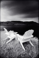 Two Adirondack chairs facing lake<br />