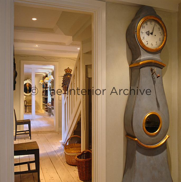 View past a Swedish grandfather clock into the staircase hall and on to the living room