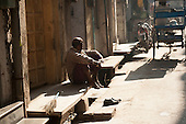 Amritsar, Punjab, India. man sitting barefoot on the step of his house with a short sweeping broom and his shoes on the steps.