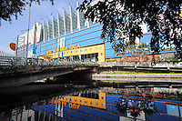 A colorful electronics market is reflected in a river in Jakarta.<br />