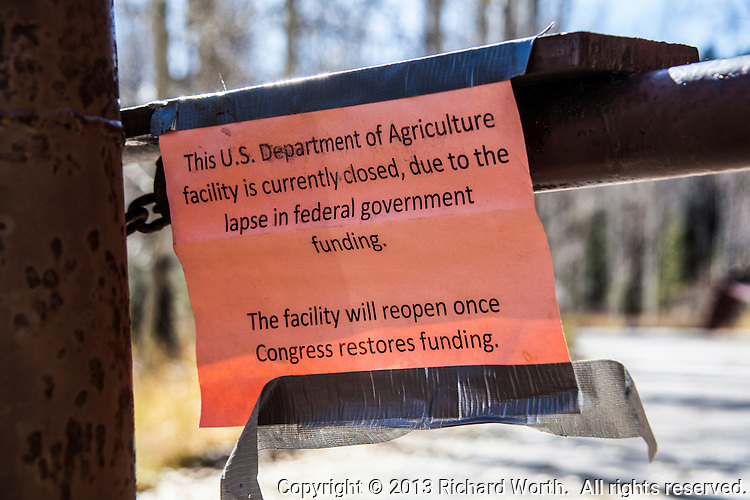 """A sign taped to the closed barrier to Sunrise Campground near Bear Lake in northeastern Utah reads, """"This U.S. Department of Agriculture facility is curently closed, due to the lapse in federal government funding.  The facility will reopen once Congress restores funding.""""  However, funding was restored after the park's usual winter closing date."""
