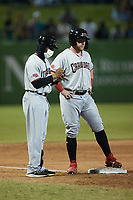 Hickory Crawdads manager Josh Johnson (1) makes notes as Blaine Crim (9) stands on third base during the game against the Greensboro Grasshoppers at First National Bank Field on May 6, 2021 in Greensboro, North Carolina. (Brian Westerholt/Four Seam Images)
