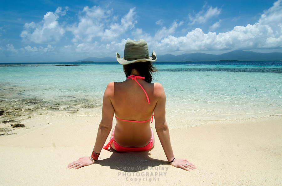 Young woman in pink bikini relaxing on sea shore of tropical turquoise water and white sand beach, San Blas Islands, Panama