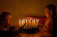 Kinder basteln einen Lichterkranz für die Adventszeit, Adventskranz, Kinder zünden die Kerzen auf dem fertigen Lichterkranz an, Lichterkranz mit 24 brennenden Kerzen für den 1. bis 24. Dezember
