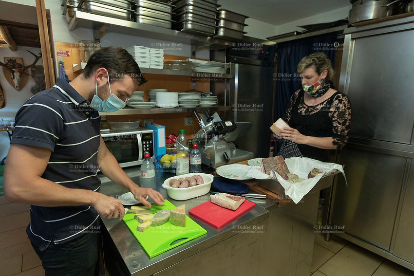 Switzerland. Canton Ticino. The family Cereghetti runs the Agriturismo Dosso dell'Ora on Monte Generoso. Luca Cereghetti (L) is helping his mother Marina in the kitchen. Luca is cutting the cheese with a knife. Marina prepares  delicatessen meat plates which will be served to customers during lunch service. The cheese is homemade. The meat comes from animals raised at the farm. The mother and son wear both a mask as prevention measure against Coronavirus (also called Covid-19). 4.07.2020 © 2020 Didier Ruef