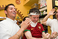 Waiter Omar Flores, left, celebrates a Portugal goal with fellow fan Rui Santos, chef, during Portugal's World Cup match with the Netherlands on June 25, 2006 at Luzia's, a restaurant in New York City.<br /> <br /> The World Cup, held every four years in different locales, is the world's pre-eminent sports tournament in the world's most popular sport, soccer (or football, as most of the world calls it).  Qualification for the World Cup is open to any country with a national team accredited by FIFA, world soccer's governing body. The first World Cup, organized by FIFA in response to the popularity of the first Olympic Games' soccer tournaments, was held in 1930 in Uruguay and was participated in by 13 nations.    <br /> <br /> As of 2010 there are 208 such teams.  The final field of the World Cup is narrowed down to 32 national teams in the three years preceding the tournament, with each region of the world allotted a specific number of spots.  <br /> <br /> The World Cup is the most widely regularly watched event in the world, with soccer teams being a source of national pride.  In most nations, the whole country is at a standstill when their team is playing in the tournament, everyone's eyes glued to their televisions or their ears to the radio, to see if their team will prevail.  While the United States in general is a conspicuous exception to the grip of World Cup fever there is one city that is a rather large exception to that rule.  In New York City, the most diverse city in a nation of immigrants, the melting pot that is America is on full display as fans of all nations gather in all possible venues to watch their teams and celebrate where they have come from.