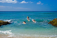 Three young women surfing at Makaha
