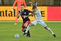 WASHINGTON, DC - SEPTEMBER 27: Gustavo Bou #7 of New England Revolution battles for the ball with Frederic Brilliant # 13 of D.C. United during a game between New England Revolution and D.C. United at Audi Field on September 27, 2020 in Washington, DC.