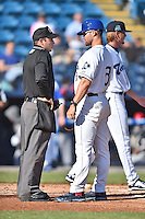 Asheville Tourists manager Warren Schaeffer (13) discusses a close play at the plate with home plate umpire Grant Conrad during game one of a double header against the Hickory Crawdads on April 21, 2015 in Asheville, North Carolina. The Crawdads defeated the Tourists 10-1. (Tony Farlow/Four Seam Images)