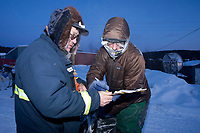 Volunteer checker and Ruby resident Billy Honea checks in Dan Kaduce at dusk in Ruby during the 2010 Iditarod