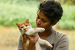 Fishing Cat (Prionailurus viverrinus) biologist, Anya Ratnayaka, holding Domestic Cat (Felis catus), Urban Fishing Cat Project, Colombo, Sri Lanka