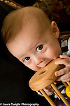 5 month old baby boy closeup holding and mouthing toy wooden cylinder holding colored balls