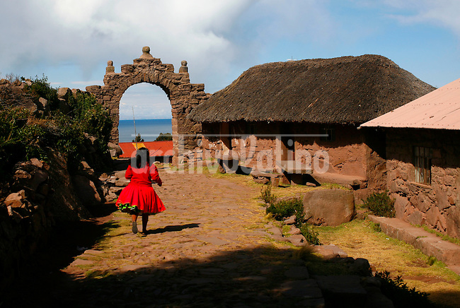 An indigenous girl runs along a path on the island of Taquile in Lake Titicaca off Puno, Peru, on May 12, 2008. The inhabitants, Taquileños, are known for their fine handwoven textiles and clothing, which are regarded as among the highest-quality handicrafts in Peru.