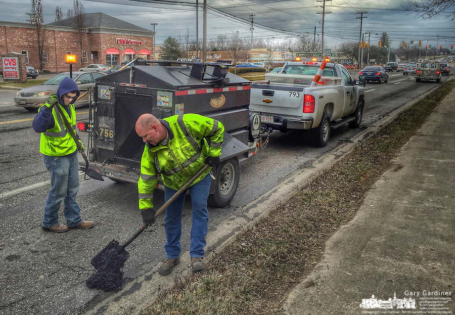 City workers fill potholes in Cleveland Ave.