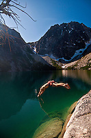 Man in shorts leaping into an emerald green alpine lake, Colchuck Lake, Alpine Lakes Wilderness, WA.