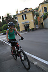 Woman biking in front of our hotel in Bogliasco, Genova, Italy.