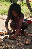 Aldeia Baú, Para State, Brazil. Kayapo girl cracking babassu nuts with a hammer on a rock, smiling.