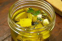 How to prepare French goat cheese (chevre) in herbs and olive oil recipe (series of pictures): put the cheese pieces in a glass jar add spices, herbs and garlic and cover with olive oil Clos des Iles Le Brusc Six Fours Cote d'Azur Var France