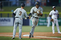 Alika Williams (6) of the Charleston RiverDogs slaps hands with third base coach Blake Butera (3) after hitting a home run during the game against the Kannapolis Cannon Ballers at Atrium Health Ballpark on June 29, 2021 in Kannapolis, North Carolina. (Brian Westerholt/Four Seam Images)