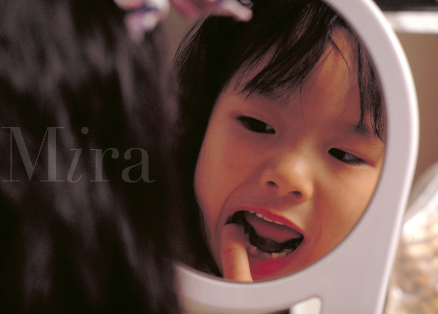 5 year old Asian-American girl looking in the mirror to check her missing baby teeth. Dental health, childhood, kids. Kimberly.