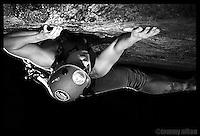 Female rock climber ascending sheer face