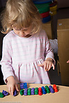 Education preschool 3-4 year olds girl linking up small color plastic vehicles by type