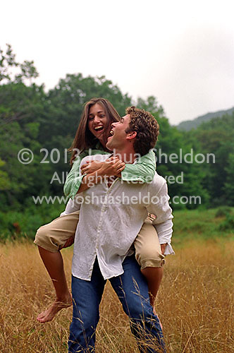 Young man giving a woman a piggy back ride<br />