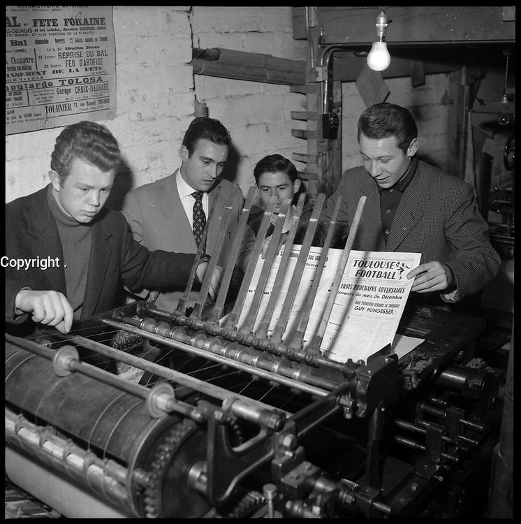 Janvier 1957. Vue d'un groupe de joueurs du Toulouse Football Club autour d'une rotative dans une imprimerie toulousaine