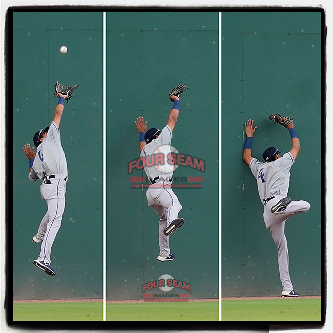 Left fielder Ramiro Rodriguez (4) of the Asheville Tourists goes high on the Green Monster wall to make a catch in a game against the Greenville Drive on Tuesday, June 1, 2021, at Fluor Field at the West End in Greenville, South Carolina. (Tom Priddy/Four Seam Images) #baseball #milb #sports #gotourists