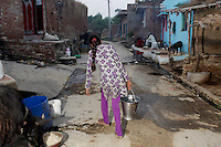 A woman from a village on the outskirts of Kanpur carries water from wells that have been sunk deep into the ground. It is feared that the severe pollution has penetrated the groundwater, allowing many harm toxins to enter the water and food chain.
