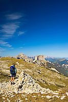 Walker stands on the summit of La Montagnette in the Drome looking towards Mt. Aiguille, Le Grand Veymont, le Sommet de Peyre-Rouge and the escarpment of the High Vercors Plateau with the Valley of the Drac on the right looking towards Grenoble, Isere. France.