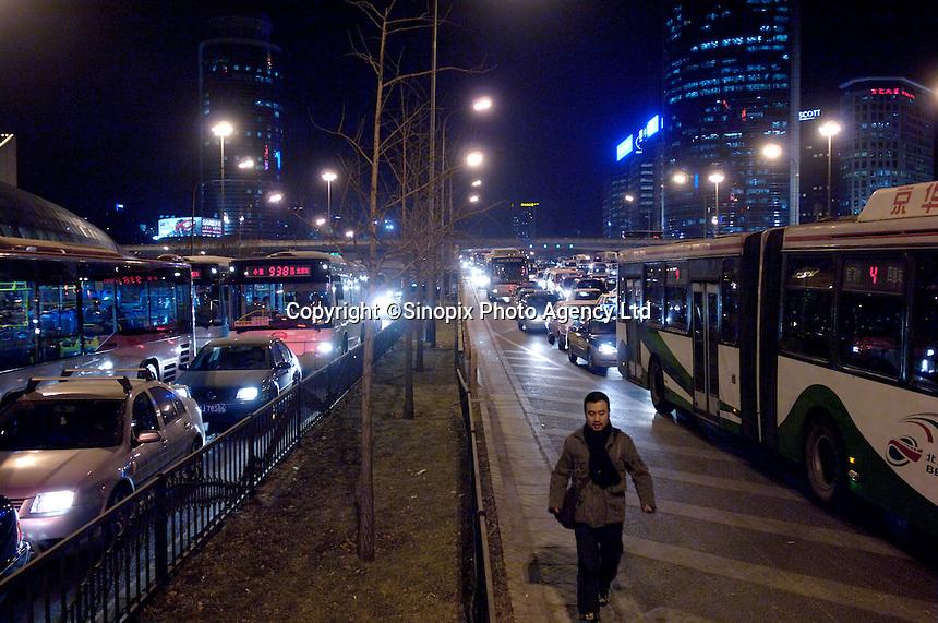 A man walks along the cars stream in CBD of Beijing, China..06 Jan 2006