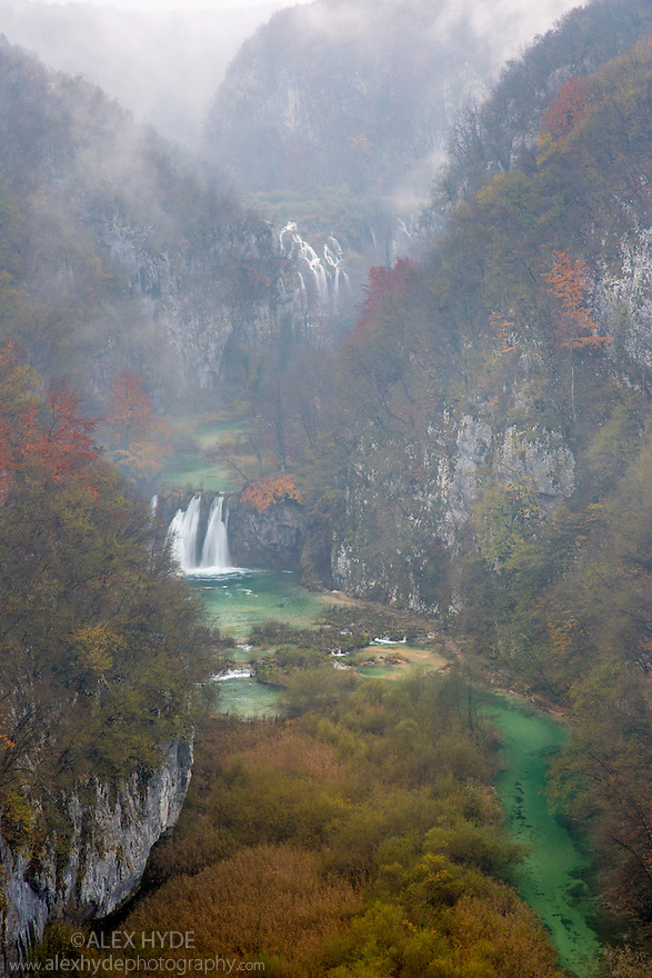 Looking up a deep limestone gorge towards the 'Sastavci' waterfalls that can be seen in the distance. Plitvice Lakes National Park, Croatia. November.