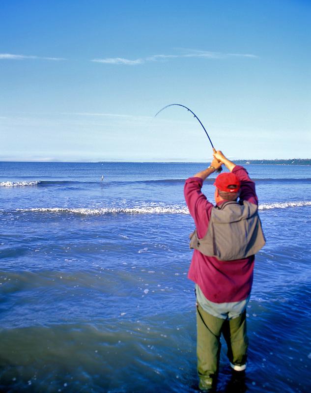 Fly fisherman playing a Sockeye Salmon on Kalgin Island, Alaska