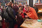 Christmas Eve Vigil Service, St. Sava Serbian Orthodox Church, Jackson, Calif...Fr. Steve Tumbas anoints the forehead of a young boy with holy oil.